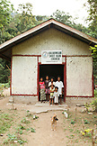 PHILIPPINES, Palawan, Barangay region, a Batak preacher and his family stand in front of the church that they built in Kalakwasan Village