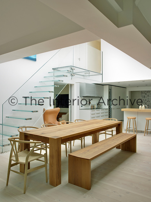 A glass staircase and a long wooden dining table perfectly match the contemporary atmosphere in this kitchen dining area