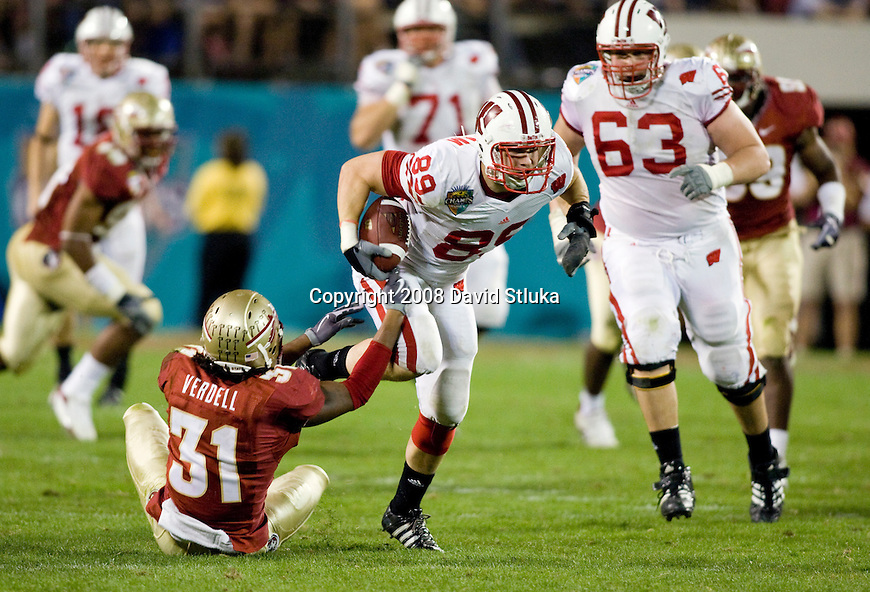 ORLANDO, FL - DECEMBER 27: Tight end Garrett Graham #89 of the Wisconsin Badgers breaks the tackle of linebacker Toddrick Verdell #31 of the Florida State Seminoles during the Champs Sports Bowl on December 27, 2008 at the Citrus Bowl in Orlando, Florida. Florido State beat Wisconsin 42-13. (Photo by David Stluka)