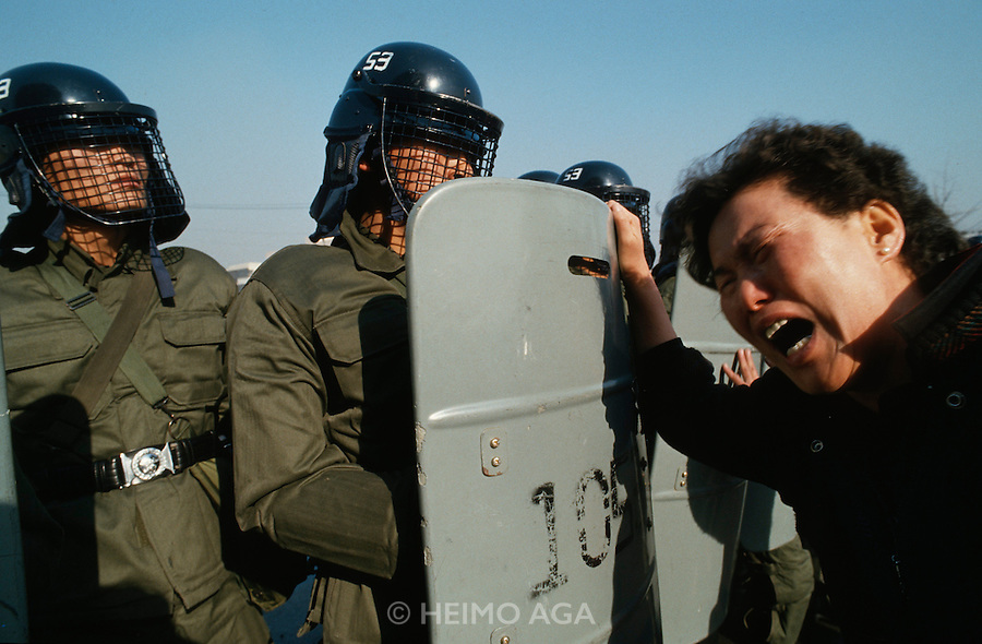Seoul, Korea. Riot police with mother demanding release of her son.