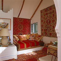 The daybed in the small whitewashed living room of the poolhouse is covered with colourful Moroccan textiles