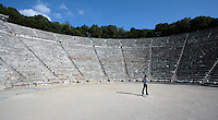 EPIDAURUS, GREECE - APRIL 14 : A low angle view of the Orchestra and Cavea of the Theatre, on April 14, 2007 in Epidaurus, Greece. The Theatre, designed by Polykleitos the Younger, was built in the late 4th century BC and extended in the Hellenistic period. It was rediscovered in 1881 and significantly restored in the 1950s.  It has the three main features of a Greek theatre: the orchestra, a sunken round stage on which someone is standing; the skene, a raised rectangular stage beyond the orchestra; and the cavea, a raked semi-circular auditorium with radiating diazomas. The theatre is renowned for its accoustics thanks to the symmetry of the cavea, which nestles in the wooded hills, seen here in the afternoon light. (Photo by Manuel Cohen)
