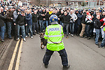 © Joel Goodman - 07973 332324 - all rights reserved . 03/04/2010 . Dudley , UK . A police dog handler wearing a riot helmet holds back a large crowd of EDL supporters . The English Defence League ( EDL ) hold a demonstration in Dudley , opposed by Unite Against Fascism ( UAF ) . Photo credit : Joel Goodman