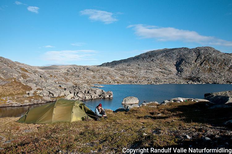 Dame i teltåpningen en sensommerkveld. ---- Woman in tent a late summer evening.