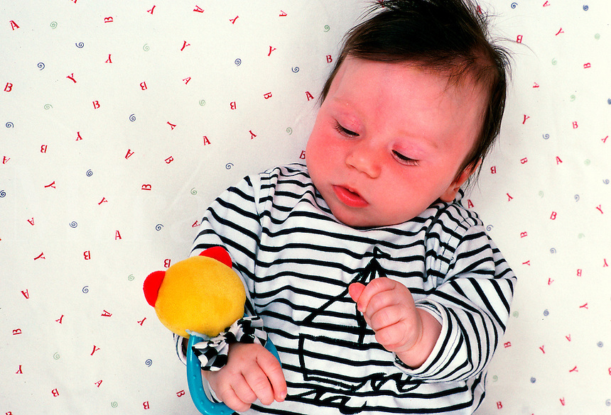 Infant child sleeps with small stuffed rattle toy in hand.
