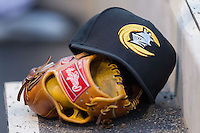 A Charlotte Knights cap sits on top of a glove in the home dugout during the International League game against the Gwinnett Braves at BB&T Ballpark on April 16, 2014 in Charlotte, North Carolina.  The Braves defeated the Knights 7-2.  (Brian Westerholt/Four Seam Images)