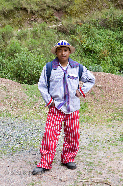 Guatemalan man in traditional clothes from Todos Santos poses on the mountainside of La Torre, outside of Todos Santos Cuchuamatan, Western Highlands, Guatemala