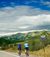 A pair of bicyclists keep pedaling rhythm along highway US20 in south central Idaho, while they appreciate the spectacular beauty of the Sawtooth Mountains and the cloudbank building above them. A small road sign urges them to adopt this highway. August 2008.
