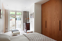 A white bedroom on the lower ground floor with a pair of French doors leading to the garden. The room is furnished in neutral tones with a built in wardrobe in a recess, double bed and a Victorian chest of drawers.