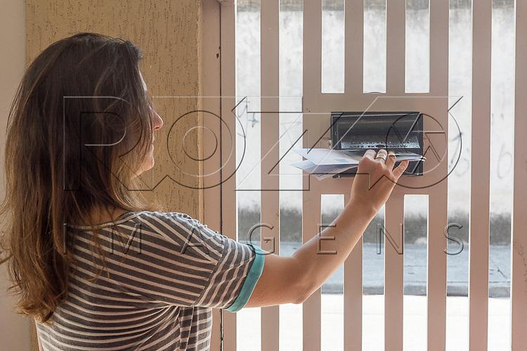 Mulher pegando correspondência na caixa de correio, 09/2017.