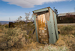 Leaning wooden outhouse with asphalt roofing and lock, Randsburg, Calif.