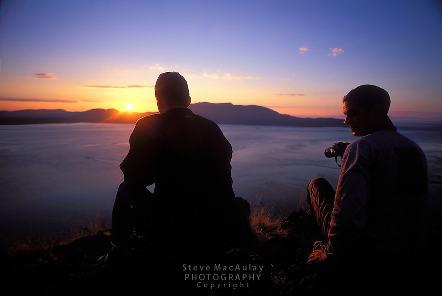 Two young men enjoy the spectacular sunset from high atop Eagle Cliff, looking across Rosario Strait, San Juan Islands, Washington