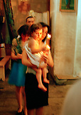 REPUBLIC OF GEORGIA, mother carrying her child and candles at a traditional baptism, Tbilisi