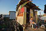 "A woman sits with her daughter outside her temporary house in Tacloban, a city in the Philippines province of Leyte that was hit hard by Typhoon Haiyan in November 2013. The storm was known locally as Yolanda. The house sits within the 40 meter ""no build"" zone in which the government has prohibited construction of houses."