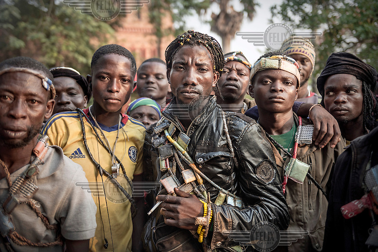 'General Gilbert' stands in the middle of a group of Anti-Balaka fighters. He is drapped in strings of Gris-Gris amulets that contain spells to protect the wearer against bullets and harm. They claim they are defending the Christian side of Boda against the Muslim side while French peace-keepers try to keep them apart.  In 2013 a rebellion by a predominantly Muslim rebel group Seleka, led by Michel Djotodia, toppled the government of President Francios Bozize. Djotodia declared that Seleka would be disbanded but as law and order collapsed the ex-Seleka fighters roamed the country committing atrocities against the civilian population. In response a vigillante group, calling themselves Anti-Balaka (Anti-Machete), sought to defend their lives and property but they then began to take reprisals against the Muslim population and the conflict became increasingly sectarian. French and Chadian peacekeeping forces have struggled to contain the situation and the smaller Muslim population began to flee the country.