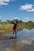 Xingu Indigenous Park, Mato Grosso State, Brazil. Aldeia Waura. Man fishing from a canoe with a bow and arrow.