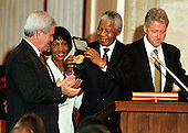 Washington, DC - September 23, 1998 -- President Nelson Mandela of South Africa shows his Congressional Gold Medal to United States House Speaker Newt Gingrich (Republican of Georgia) on Wednesday, September 23, 1998. Pictured left to right are: Speaker of the United States House of Representatives Newt Gingrich (Republican of Georgia); United States Representative Maxine Waters (Democrat of California); President Mandela; and United States President Bill Clinton...Credit: Ron Sachs / CNP