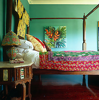 Side view of a four poster bed which is covered in a colourful textile and has a Japanese kimono as a headboard