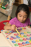 Education preschool 3-4 year olds girl using magnetic wand to move letters into positon in alphabet puzzle