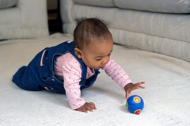 Richmond, CA African American baby girl, seven months old, reaching for rattle using palmar grasp MR