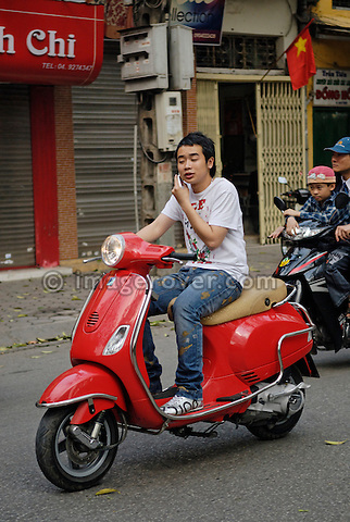 Asia, Vietnam, Hanoi. Hanoi old quarter. Cool young vietnamese man using a mobile phone while riding a red Vespa motorbike through Hanoi.