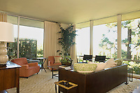 A pair of coral coloured club chairs sit opposite a brown leather sofa in the living room