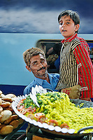 Food vendor at Udaipur train station proudly showing off his young son, Udaipur, India.