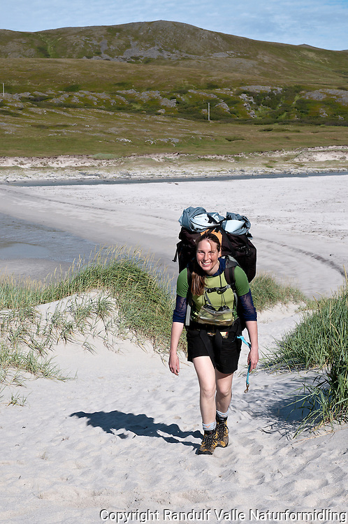 Dame med ryggsekk på sandstranda Sandfjellsanden på Sørøya. ---- Woman walking on sandy beach at Sørøya.