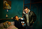 SPAIN, Madrid : Spanish Vicente Torres, 73, lies in his bed while his grandson Jonathan Torres (R) and his sister-in-law Maria Mostajo (C) cry in his appartment in Madrid on April 18, 2012. Torres, who is severy ill and underwent a recent heart surgery, faces an eviction from his house. Eviction procedures in Spanish courts for unpaid mortgages and rent hit a record of 58,241 in 2011, a 21.2 percent rise over the previous year. Evictions have soared in Spain since the collapse of a property bubble in 2008 that triggered the country's economic crisis. (c) Pedro ARMESTRE