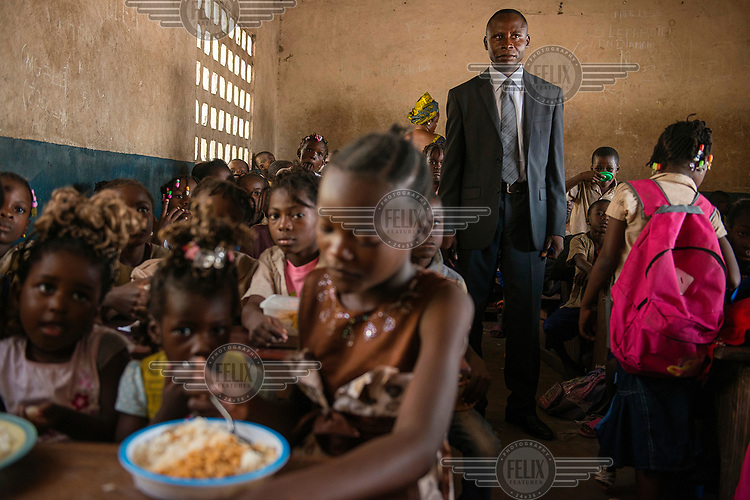 The headmaster stands in a class as the pupils eating a meal provided by an NGO as part of a 'Food for Education' program where children are given a meal as long as they attend school.