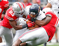 Ohio State Buckeyes safety Tyvis Powell (23) and Ohio State Buckeyes linebacker Curtis Grant (14) tackle Kent State Golden Flashes running back Anthony Meray (21) in the 1st quarter of their game in Ohio Stadium on September 13, 2014.  (Dispatch photo by Kyle Robertson)