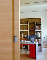 The office is divided from the main living space by a wall of storage on one side and a sliding partition on the other