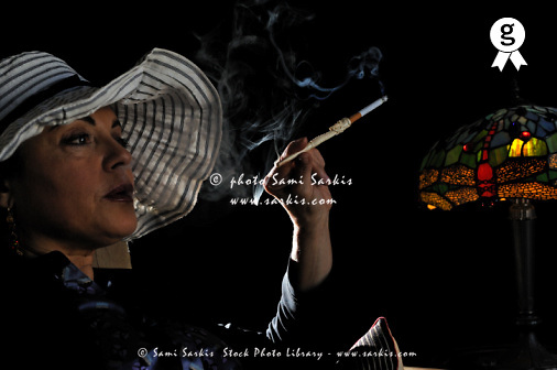 Mature woman smoking with cigarette holder (Licence this image exclusively with Getty: http://www.gettyimages.com/detail/97428406 )