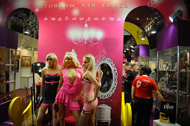 At the X-Show in Moscow, a show with stands selling and promoting businesses involved in the erotic industry, girls, handing out flyers, stopped for a photo. Moscow, Russia, May 28, 2010