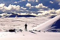A snowboarder stands on the stark snow covered landscape on the top of Mauna Kea mountain on the Big Island of Hawaii.
