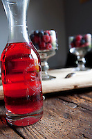 An engraved 19th century carafe accompanies a pair of stem glasses filled with fresh berries on the dining table