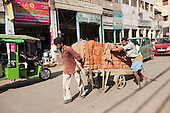Delhi, India. Three men pushing a dilapidated wooden hand-cart with metal wheeels laden with new red bricks along a city road.