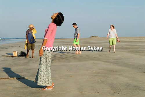 Ngwe Hsaung beach resort. Local woman laughing, European tourists watching fishermen bring their nights catch in. Myanmar Burma 2011.