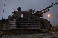 Iraqi tankers from the 1st company, 1st armour battalion of the 1st mechanized Iraqi Army Brigade operate at night   while conducting  patrols, check points and observation posts on code name route Michigan, the main road of Ramadi in the week during the national election on TUE Dec 13 2005 in Ramadi, Iraq. 1st company is part of the first armor battalion of the New Iraqi Army. it has started its training in January 2005. after 50 days their 35 russian and chinese built T 55 tanks begun conducting operations under the guidance of a US military adivisor team. in April 2005 they patrolled in the Abu Ghraib area concluding their first significant mission. While these old tanks are rolling on the ramadi streets more modern T72s are getting ready to become fully operational in Taji, their main base. the Iraqi army wanted to show their power in ramadi during the Dec 15 elections displaying their new armour company. but like all the other Iraqi forces they are not going to secure the polling sites, staying in the rear with the rest of the iraqi and coalition forces. T 55s are very old tanks. production begun in the late 50s to the late 70s. athough obsolete many countries still use the T55 as their main heavy armoured combat vehicle. slow, heavvy and with very little room for the crew it suffers from many mechanical problems constantly challenging the iraqi mechanics and engineers.
