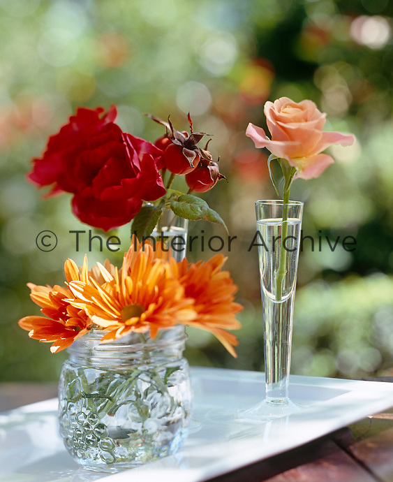 Single blooms in a variety of glass vases add splashes of colour to an autumn themed evening