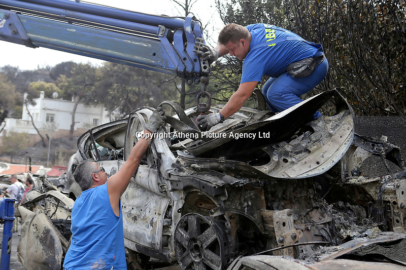 Pictured: A recovery of burned cars under way in the aftermath of the forest fire which has claimed dozens of lives in the Mati area of Rafina, Greece. Tuesday 24 July 2018<br /> Re: Deaths caused by wild forest fires throughout Greece.