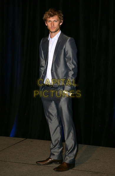 ALEX PETTYFER .CBS Films ShoWest Luncheon at the Paris Resort Hotel and Casino,  Las Vegas, Nevada, USA,.18th March 2010..full length grey gray suit hands in pockets white shirt  .CAP/ADM/MJT.© MJT/AdMedia/Capital Pictures.