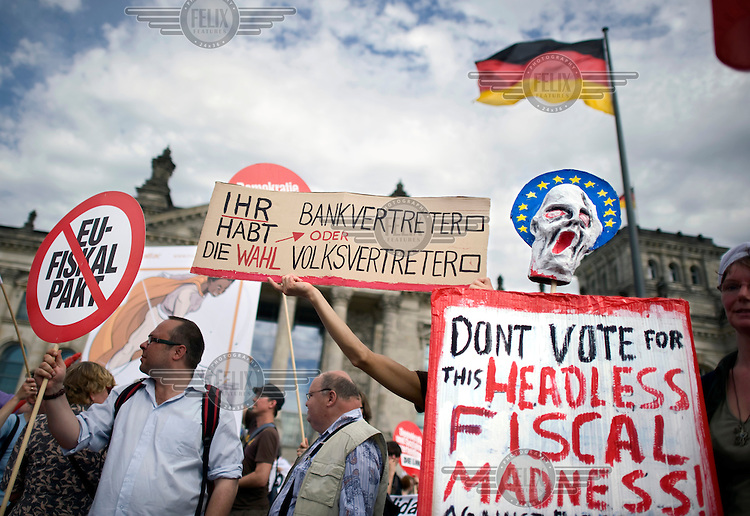 A mask in the form of Edvard Munch's The Scream is held up surrounded by a halo in the form of the European flag and a poster reading 'Don't vote for this headless fiscal madness! Against Europen fiscal compact! For a social and multicultural Europe!' at a demonstration against the EU fiscal pact outside the Reichstag in Berlin. Bundestag members are set to vote on ratification of the fiscal pact and the ESM (European Stability Mechanism) inside the parliament. Left wing party Die Linke are past of the protest.