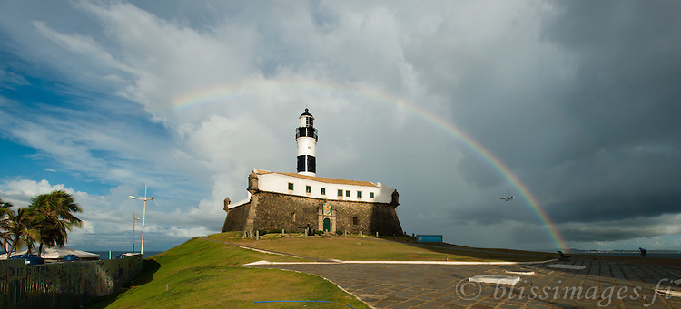 An early morning rainbow arcs over Farol da Barra fortress lighthouse in Salvador, Brazil.