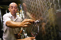 Sylvain Fadat Domaine d'Aupilhac. Montpeyroux. Languedoc. Pouring a wine sample in a glass. Stainless steel fermentation and storage tanks. Tank spout. Owner winemaker. France. Europe.