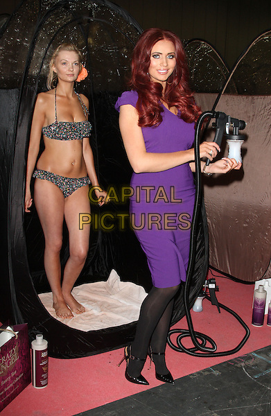 Amy Childs .appears at the Professional Beauty Show at Excel Centre, London, England..February 25th 2013.full length dress black tights model bikini side purple bottle .CAP/ROS.©Steve Ross/Capital Pictures..