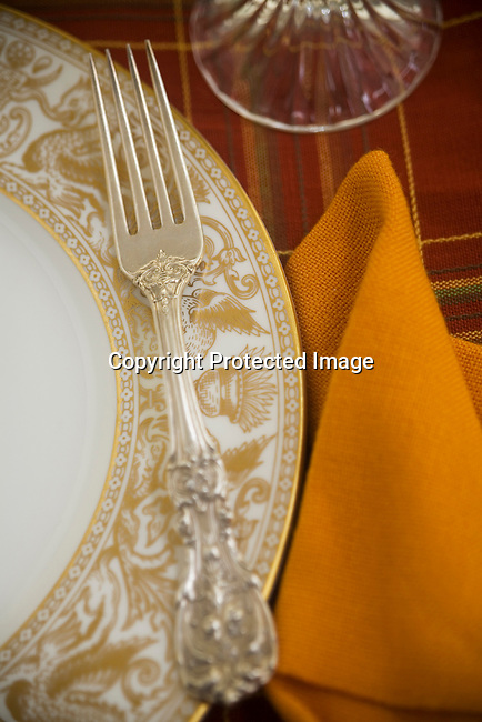 Extremely shallow depth of field on expensive silver and fine china place setting.