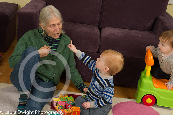 20 month old fraternal twin boys with grandmother, grandmother talking as one child points at her and she indicates herself with hand; child care takes care of grandsons twice a week