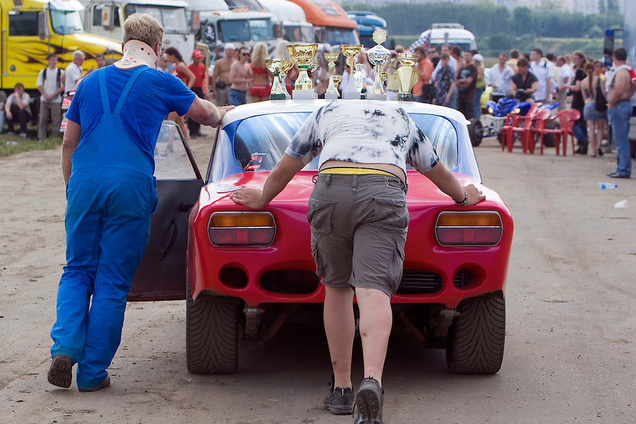 Moscow, Russia 13/07/2008..An injured competitor pushes his malfunctioning car at the annual Autoexotica Show, a ten day festival that attracts thousands of Russian motor enthusiasts.  Figures show the Russian auto market has just overtaken Germany's to become the largest in Europe, and analysts predict that within four years it will be the third largest in the world.