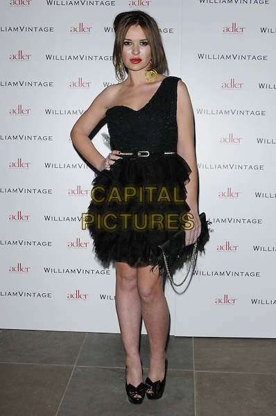 Kierston Wareing.attended the WilliamVintage & Gillian Anderson private dinner, St Pancras Renaissance Hiotel, Euston Rd., London, England, UK, .10th February 2012..full length black one shoulder strap dress belt tulle ruffle ruffle layered pep toe shoes hand on hip .CAP/CAN.©Can Nguyen/Capital Pictures.
